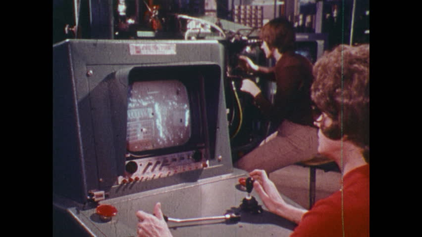 UNITED STATES 1970s: Women working with machines, zoom in on woman / Close up of microchip / Man adjusts equipment, pan to man looking at car engine / Car driving. | Shutterstock HD Video #24670997
