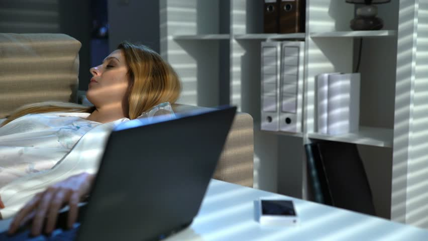 Tired businesswoman sleeping on the couch in the office with laptop and phone at night. Dolly shot | Shutterstock HD Video #24693977