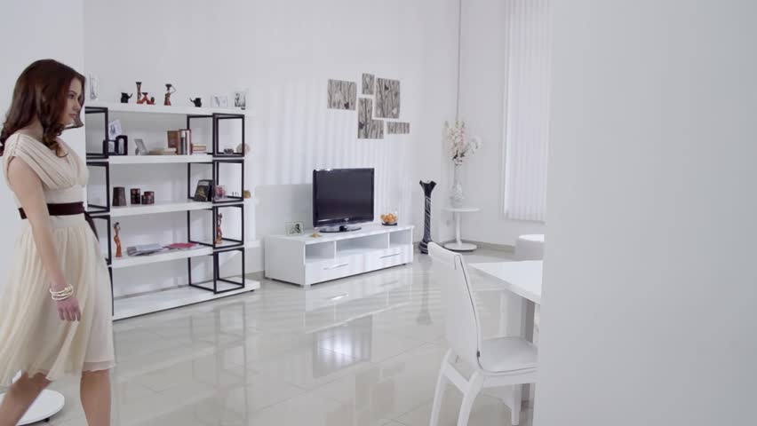 Beautiful young woman in a beige dress moves in the interior in the living room in slow motion. Slow motion family home part 1 of 15