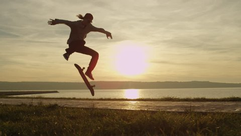 SLOW MOTION, CLOSE UP: Silhouetted skateboarder skateboarding and jumping hardflip trick on boulevard along the ocean at golden light sunset. Skateboarder riding skateboard at sunrise at seaside