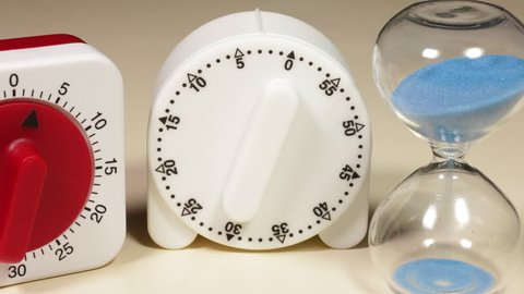 Time lapse of three kitchen timers, two clockwork and one hour glass, all set at the same time. A three minute cookery countdown.