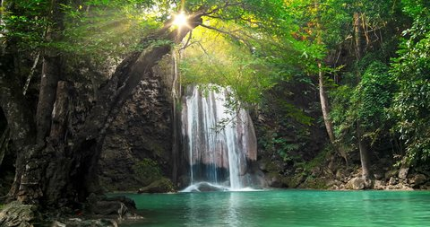 Majestic waterfall and beautiful tropical nature with sun light shining through tree branches in Erawan national park, Kanchanaburi, Thailand