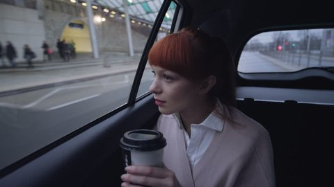 Woman in the Car Holding a Coffee Bin in her Hand
