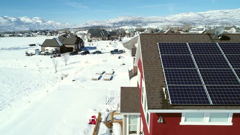 An aerial shot of a house with solar panels on its roof during the wintertime in a mountain valley with a small town