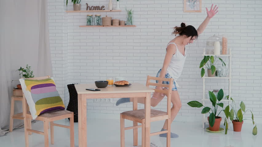 Funny young woman dancing in kitchen wearing pajamas in the morning. Brunette girl in cheerful mood listens music. | Shutterstock HD Video #24761177
