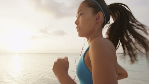 Determined female runner jogging at beach during sunset. Sporty young woman is listening music through earphones against sky wearing blue sports bra. SLOW MOTION, STEADICAM, RED EPIC.