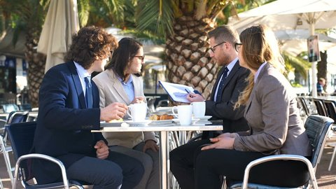 Happy businesspeople looking on diagram and discuss outcomes