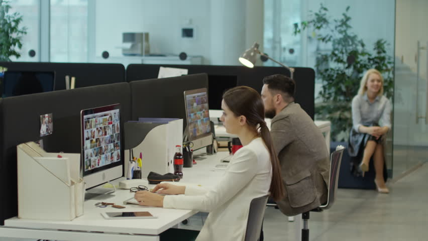 Tracking shot of modern comfortable office: one man eating pizza in workplace and putting feet on table; office workers surfing the Net on computers and two businesswomen speaking in the background | Shutterstock HD Video #24787907
