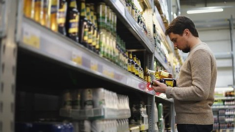The young man chooses a beer for bbq party with friends in the supermarket.