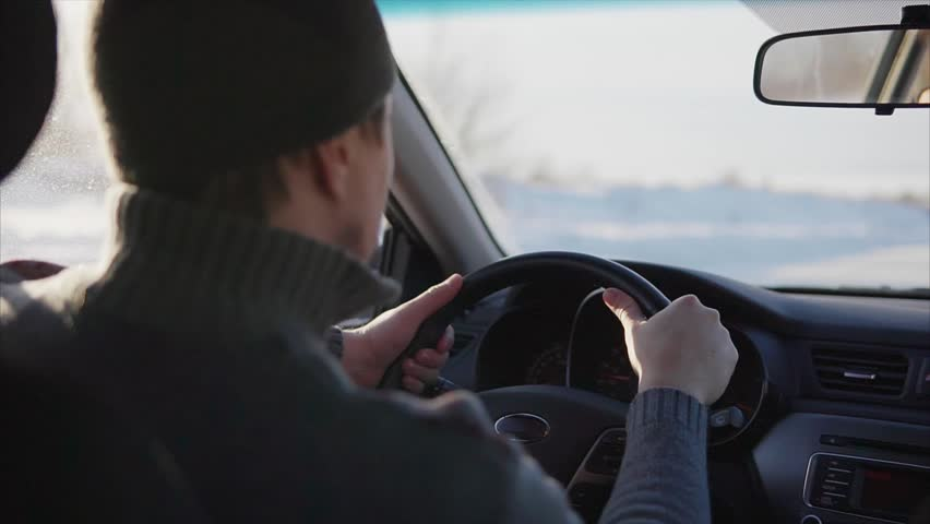 The young man slowly driving a car on a winter road. In winter, the majority of motorists still goes slow down and be careful.