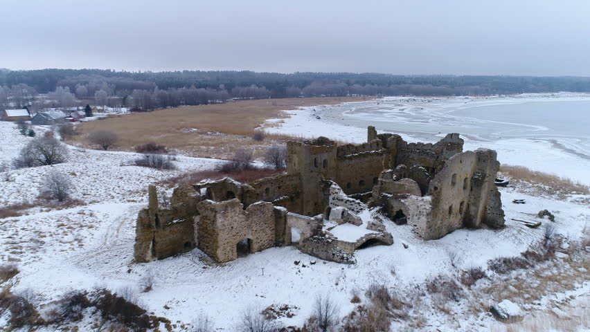The view of the old Toolse castle and the snow filled ground surrounding the ruined castle in Estonia