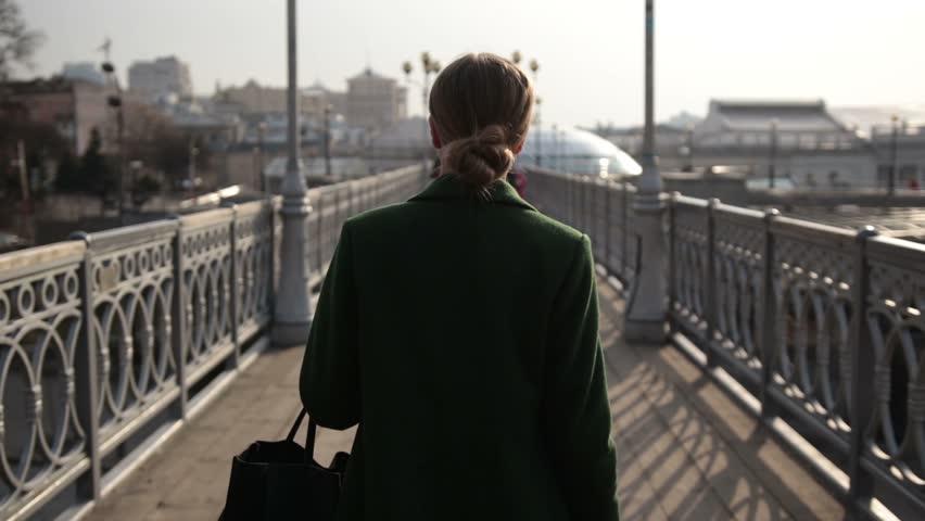 Back view of woman walking away on bridge