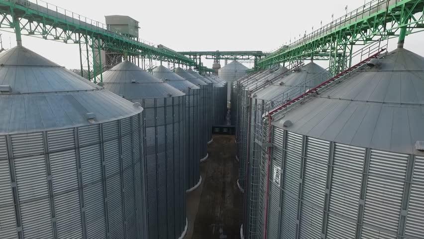 Aerial. Agriculture grain silos storage tank.  Flying near silos tanks