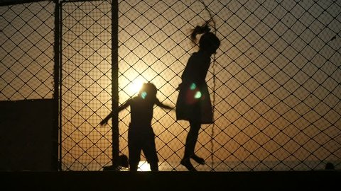 silhouettes of boy and girl jumping on the trampoline on a background of ocean sunset backlit
