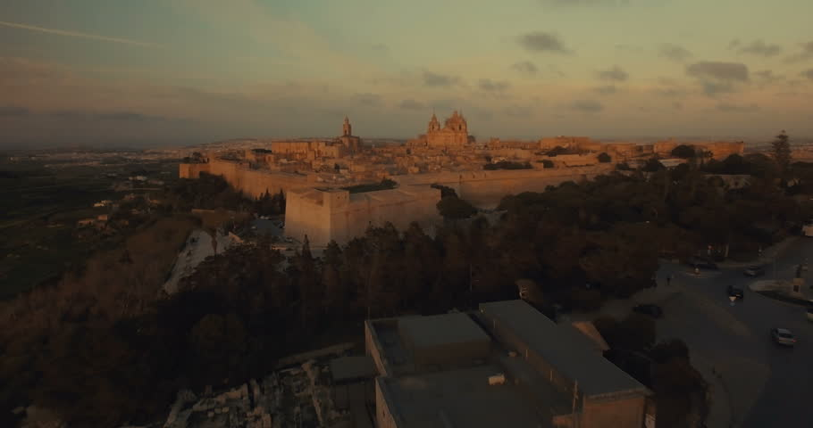 Aerial shot flying towards the church in Mdina during sunset