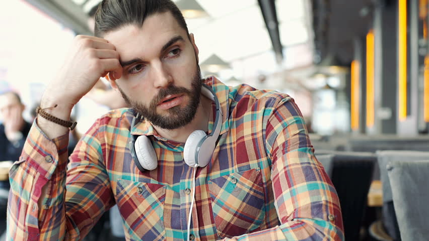 Man looks worried while thinking about something in the cafe, steadycam shot  | Shutterstock HD Video #24895577