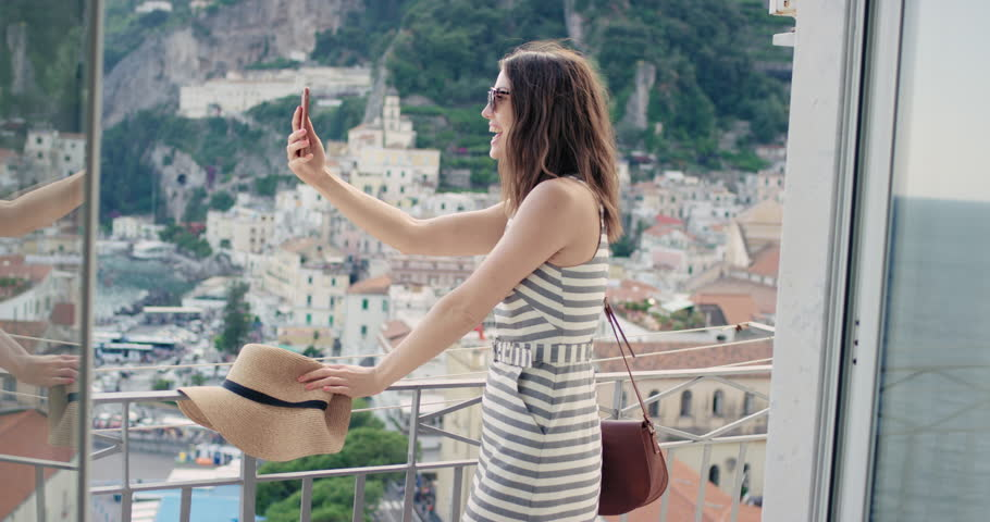 Tourist woman having video chat showing view sharing authentic travel experience from hotel balcony at sunset using smart phone connecting with friends on social media summer vacation in Amalfi Italy