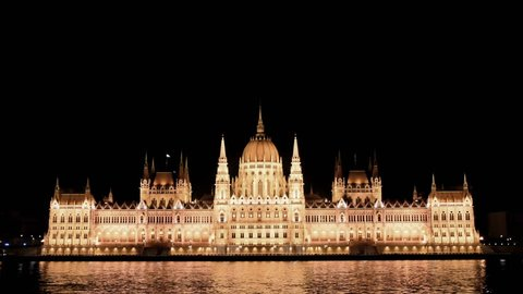 Hungarian Parliament Building at night with the River Danube in the foreground.