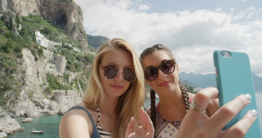 Tourist Woman taking selfie photo with smart phone Best friends sharing moment photographing Amalfi Coast Italy on European summer vacation travel adventure