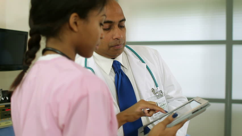 Nurse informs the doctor of a patients test results using an electronic tablet pc.