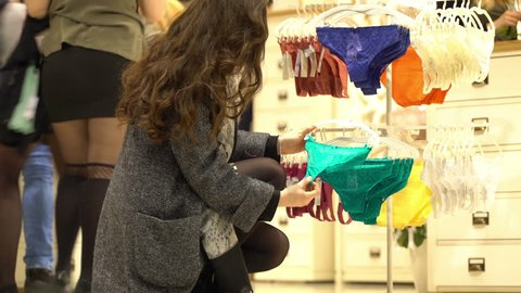 Concept festive stir in women's underwear shop in mall. Girl chooses panties and bra. Concept of shop of intimate clothes. Panties and bras hang on hangers. Shoppers come in and out of lingerie store