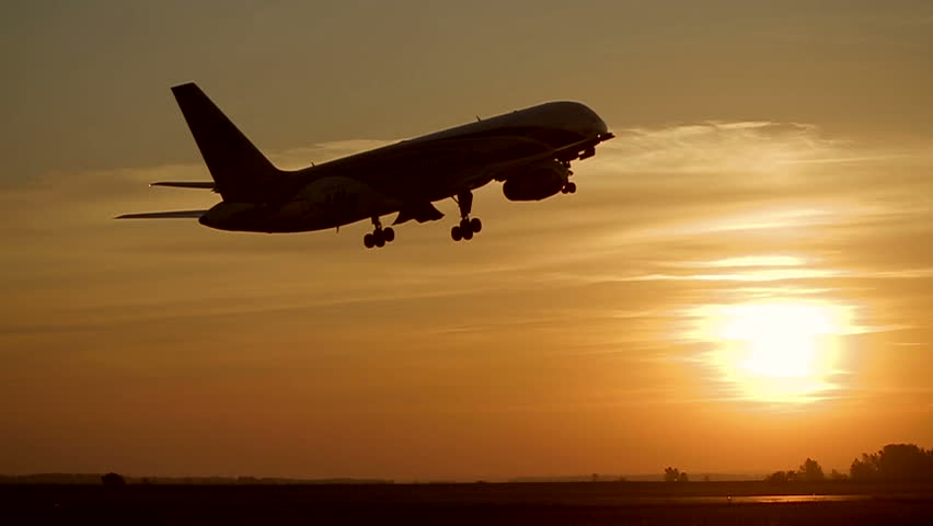 Plane takes off at sunrise background