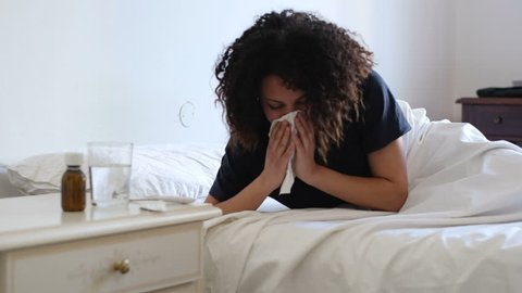 The video is about a sick and ill black afro american woman . She's lying on the bed and sneezing her nose.The framing of the clip is fixed.