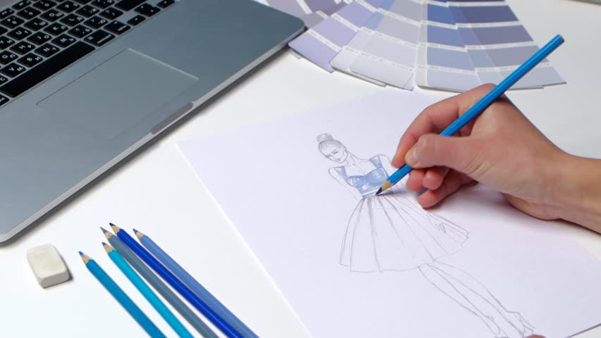 Designer With A Pencil Sketch Decorates Dresses In Blue Close Up