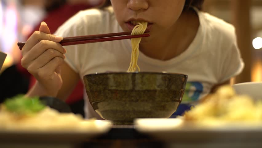 4K Asian woman eating beef noodles for dinner in a restaurant. Using sticks for eat the hot traditional chinese food-Dan