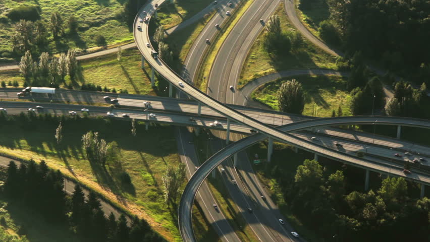 Aerial perspective of interstate commuter traffic crossing bridge on clear, early morning | Shutterstock HD Video #2499497