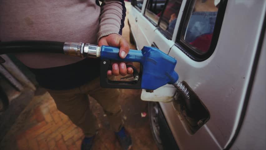 Close view of man's hands holding petrol pump. Refuelling car at petrol station. Kathmandu, Nepal