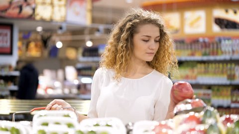 Cute 20s blonde model with long curly hair make purchases in department store closeup. Sweet female buyer select lemon, garnet for family breathing their flavor and put products in basket holding hand