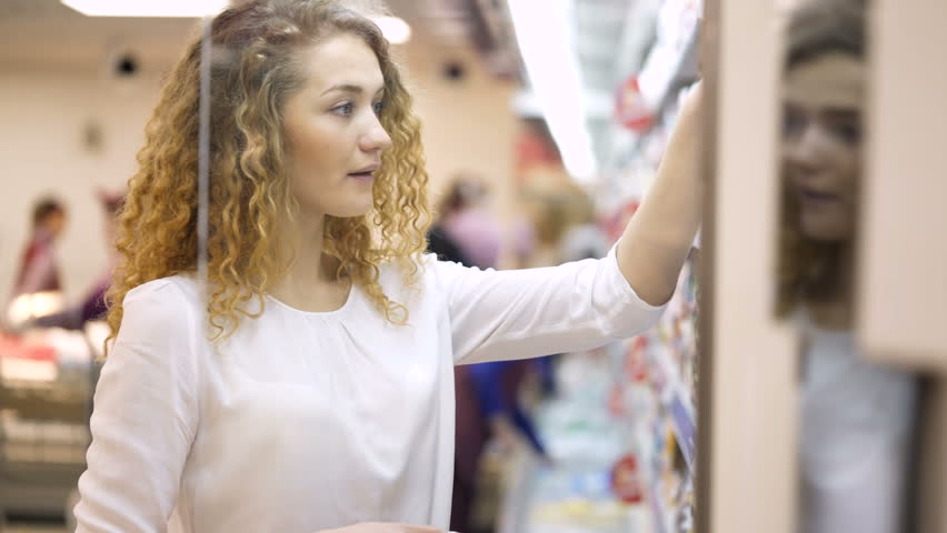 Sale, shopping, consumerism people. woman with shopping basket choosing products in supermarket. Girl in market choosing bottle from the fridge | Shutterstock HD Video #25025117
