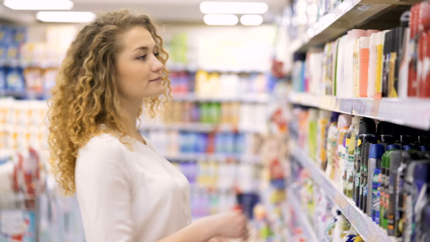 Beautiful female looking at cosmetics in supermarket. pretty Woman Choosing Body Care Products In Supermarket. Shopping in the store | Shutterstock HD Video #25025147