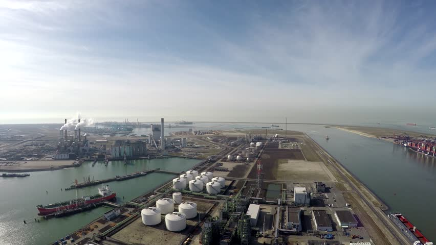 Aerial flight over harbor area industrial landscape oil storage containers below for oil reserves and also showing industry and tanker ship docked clear blue water and crisp blue sky in background 4k