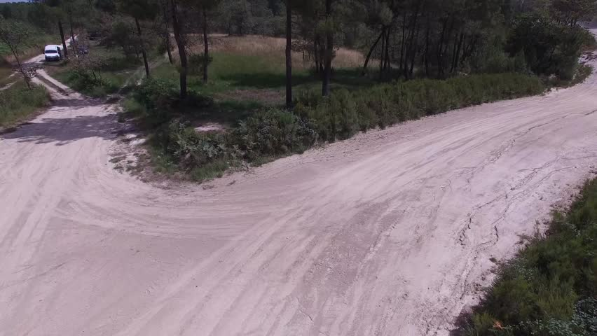 Reverse aerial shot of subaru rally car driving under the drone