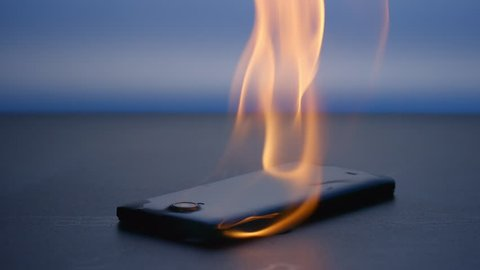 SLOW MOTION: Smart phone lies and burning on a table in the night