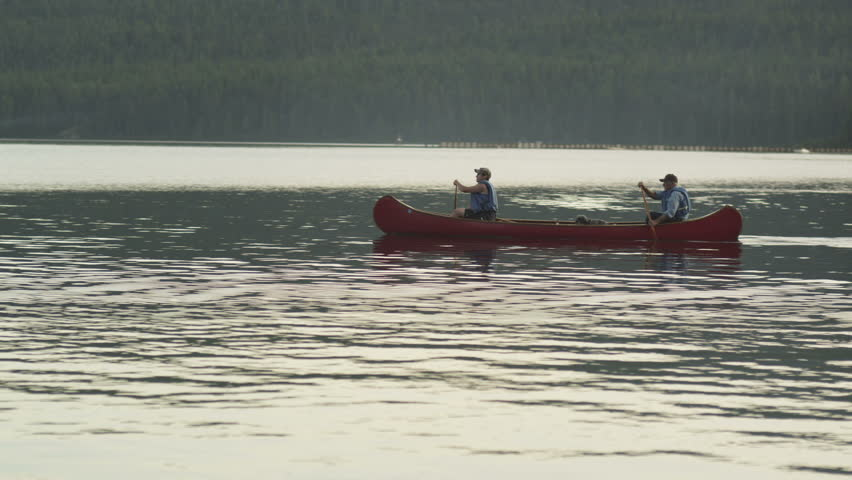 Two paddlers and their dog canoe on Idaho's Priest Lake.