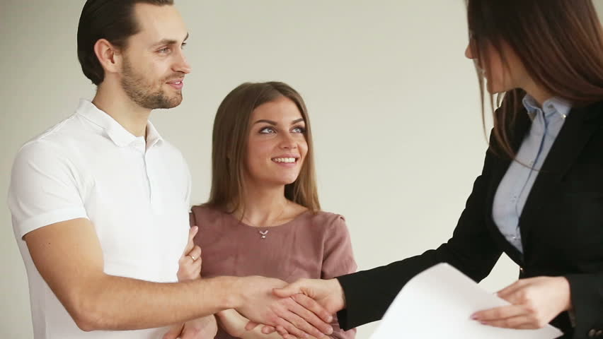 Young attractive happy smiling couple meeting real-estate agent. Overjoyed husband and wife choosing and buying new house, shaking hands with female broker, getting keys and embracing each other
