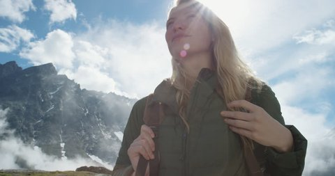 Close up portrait of Woman at top of mountain in nature with blonde hair blowing in wind above the clouds view Hiker Girl in Norway Slow Motion