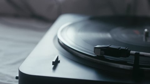CINEMAGRAPH - seamless loop. Vinyl record is being played on a modern turntable on bed. 4K UHD RAW edited footage