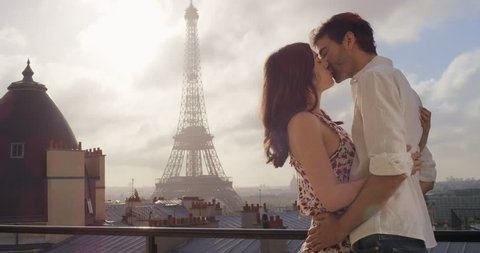 Romantic couple in Paris Eiffel Tower embrace kissing honeymoon enjoying European summer holiday travel vacation adventure