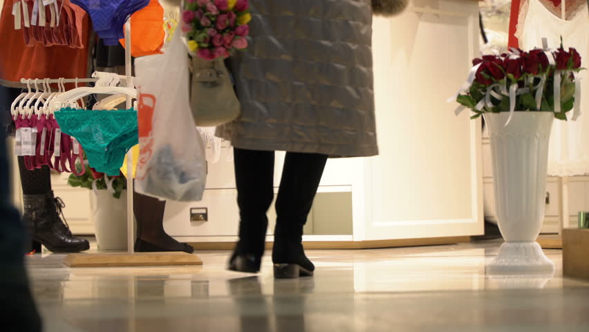 Woman with a bouquet of flowers on the eve of a holiday in an underwear store. Roses and tulips as a symbol of tenderness. Concept of shop of intimate clothes. Panties and bras hang on hangers. All