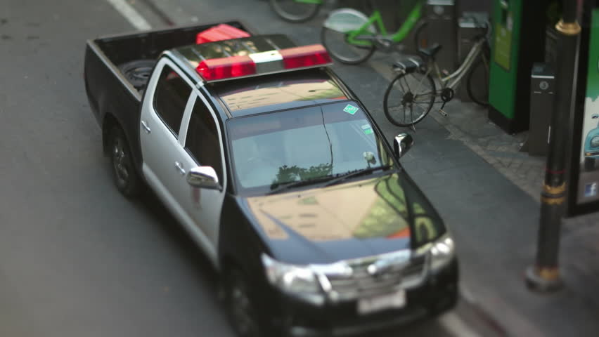 BANGKOK, THAILAND - MAY 2016: closeup view of law enforcement vehicle parked on road. Aerial view with miniature effect using Tilt&Shift lens | Shutterstock HD Video #25109477