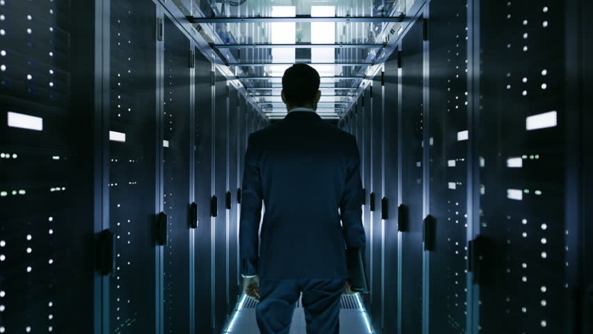 Data Center Technician Walking Through Server Rack Corridor Visually Inspecting Working Server Cabinets. Shot on RED EPIC-W 8K Helium Cinema Camera. | Shutterstock HD Video #25117001