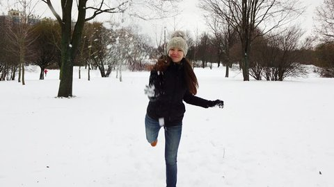 Funny playful girl throw big snowball straight to camera and hit target, white splashes fly around. Cute young adult woman take snow and strike it forward, snow slowly fall down, successful shoot