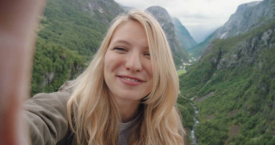 Beautiful woman taking selfie video using smartphone outdoors Girl sharing photograph on social media with mobile phone enjoying Norway vacation travel adventure #25126247