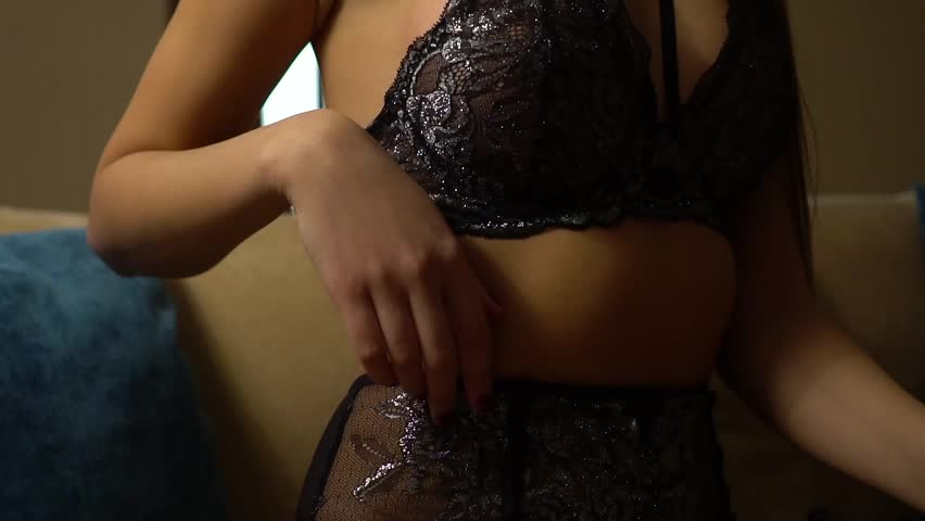 Young sexy long-haired girl in elegant underwear sits on the couch and gently touches herself with her hand. | Shutterstock HD Video #25131917