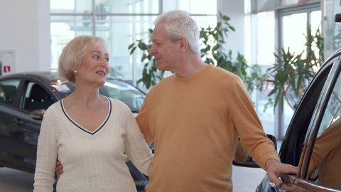 Attractive senior couple buying the car at the dealership. Gray caucasian man embracing his wife against background of new sedan. Aged blond woman showing car key near her husband
