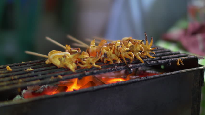 Traditional street food of Thailand. Cooking small squids on the grill at night streetfood fair